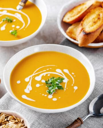 butternut squash soup with sour cream and cilantro served in a white bowl