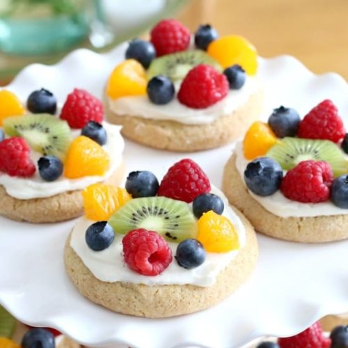 Pick up some nice and soft sugar cookies from your local bakery and top with a delicious cream cheese topping and fruit to make these Individual Fruit Pizzas! They're so good!