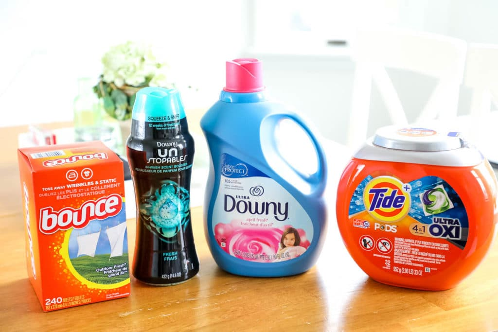 tide pods, downy fabric softener, downy unstoppables, bounce dryer sheets, on a table