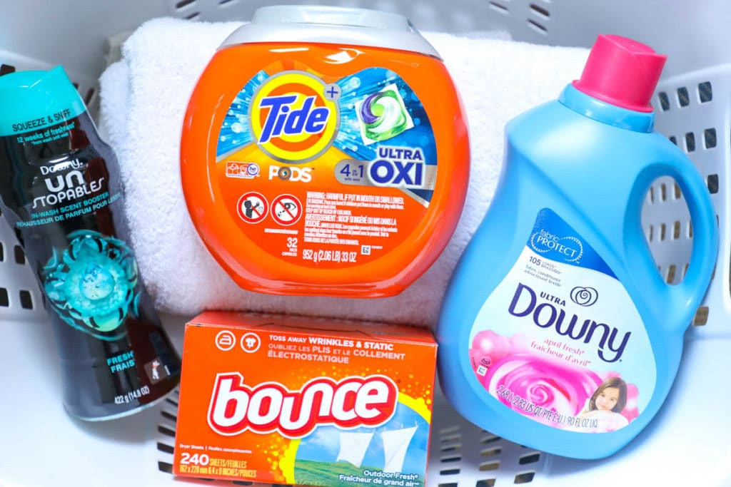 tide, bounce, downy, unstoppables in a clothes basket