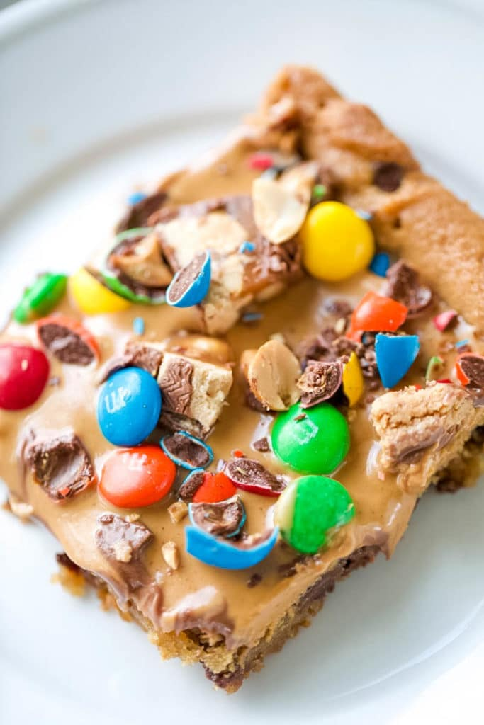 Skip all the hassle of measuring, mixing and scooping cookie dough and create this Chocolate Chip Candy Cookie Bar. With all the fun flavors of a chocolate chip cookie with loads of candy bar toppings and peanut butter, make these Chocolate Chip Cookie Bars exceptionally special! #chocolatechipcookiebars #chocolatechipcookies #chocolate #cookies #peanutbutter | allthingsmamma.com