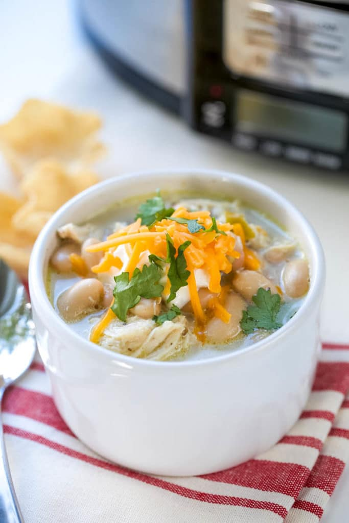 This Easy White Chicken Chili is the perfect slow cooker weeknight meal! Creamy with plenty of toppings, this soup recipe is the perfect way to end the day!