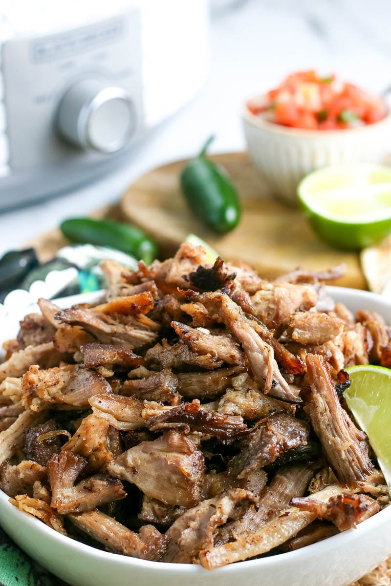 slow cooker carnitas  in a bowl with a lime wedge