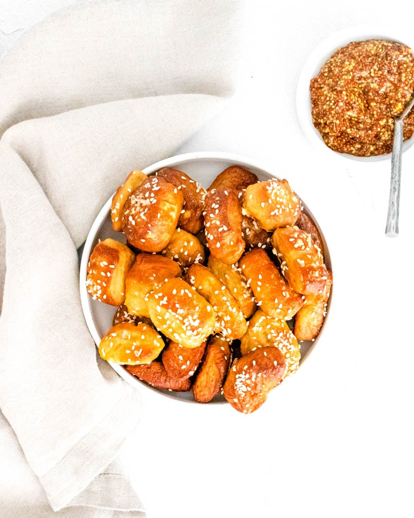 Small pretzel bites topped with kosher salt in white bowl, next to small bowl of crushed nuts and spoon