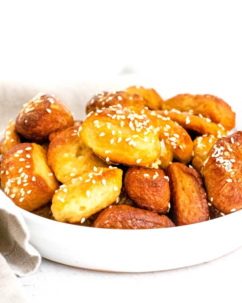 Small pretzel bites topped with kosher salt in white bowl