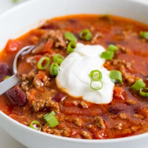 Image of easy slow cooker ground beef chili with beans in a white bowl, topped with sour cream and fresh scallions. A silver spoon is dipped in the bowl.