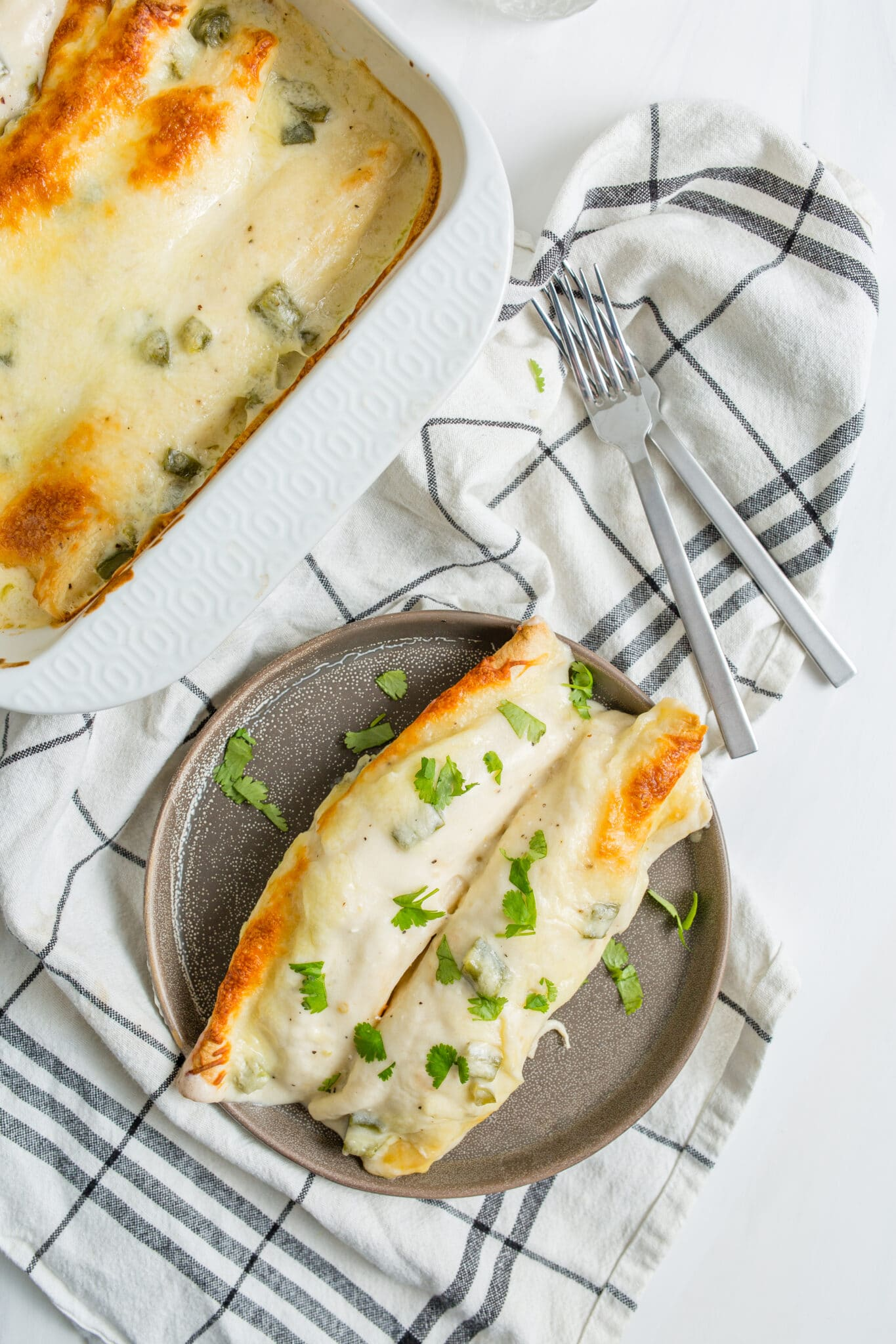 Top shot of white chicken enchiladas in baking dish and on plate next to two forks.