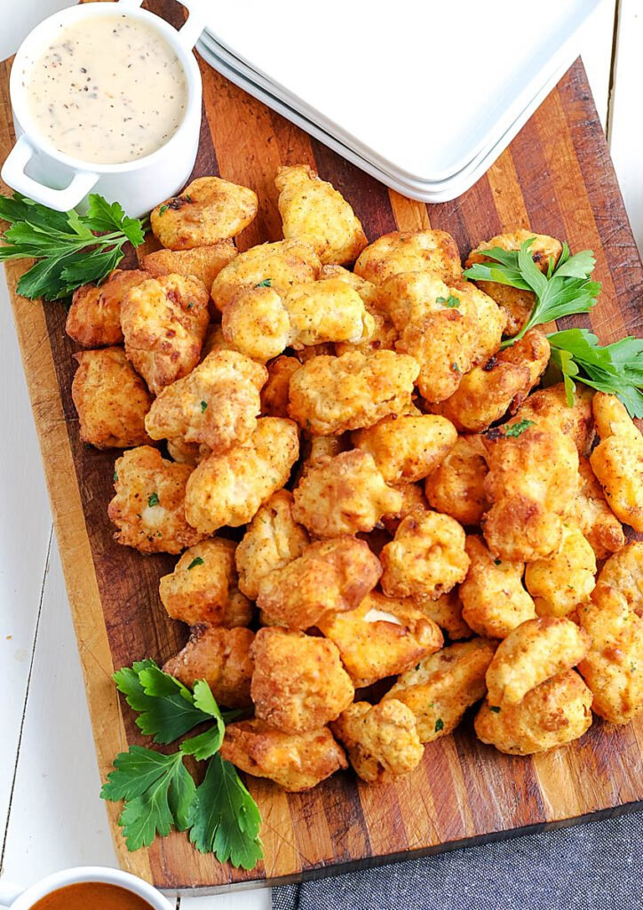 air fryer popcorn chicken on a cutting board with dipping sauces