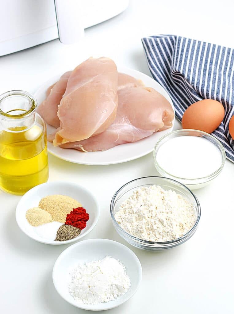 air fryer popcorn chicken ingredients on a table - chicken, flour, spices, buttermilk, olive oil