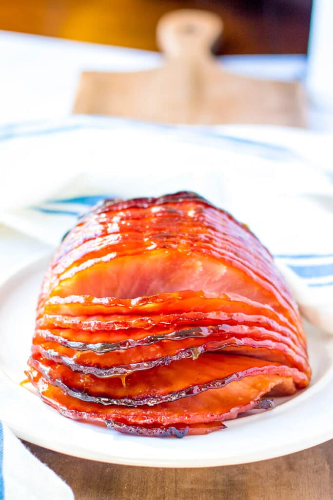 A spiral cut ham is presented on a white plate.