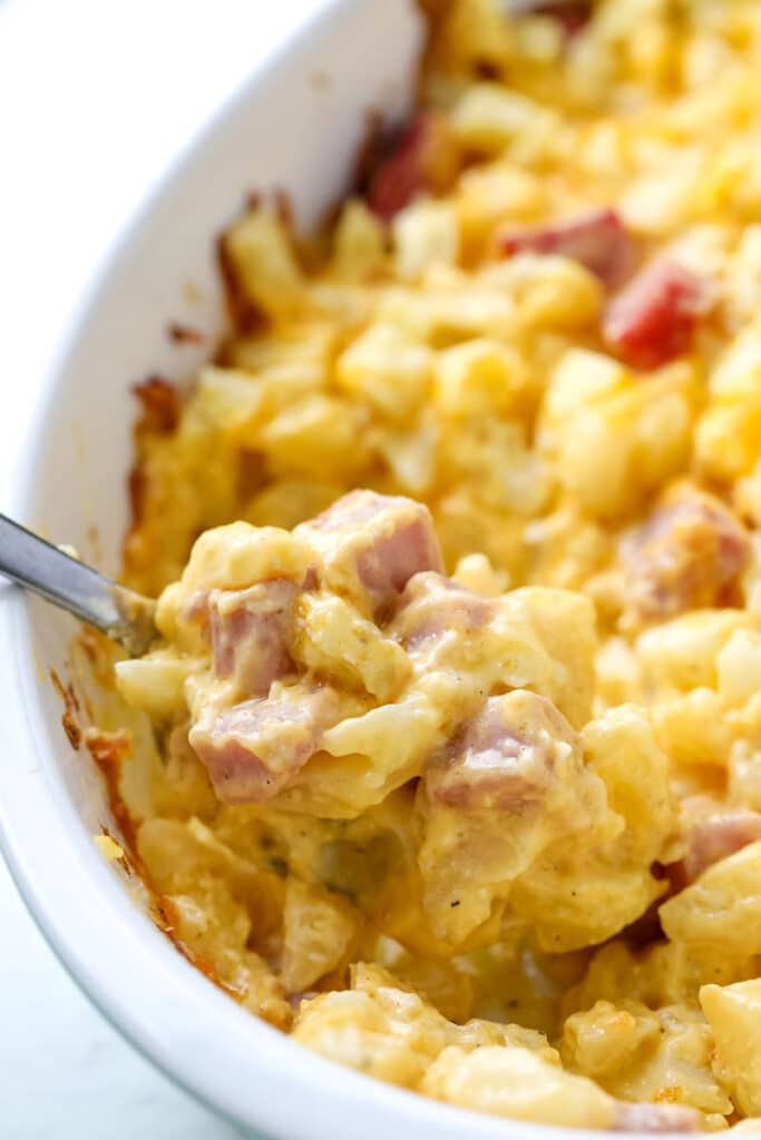 Ham and cheesy potato casserole is being served out of a white baking dish.