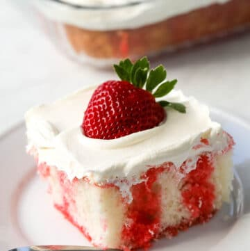 A slice of strawberry poke cake is presented on a white plate.