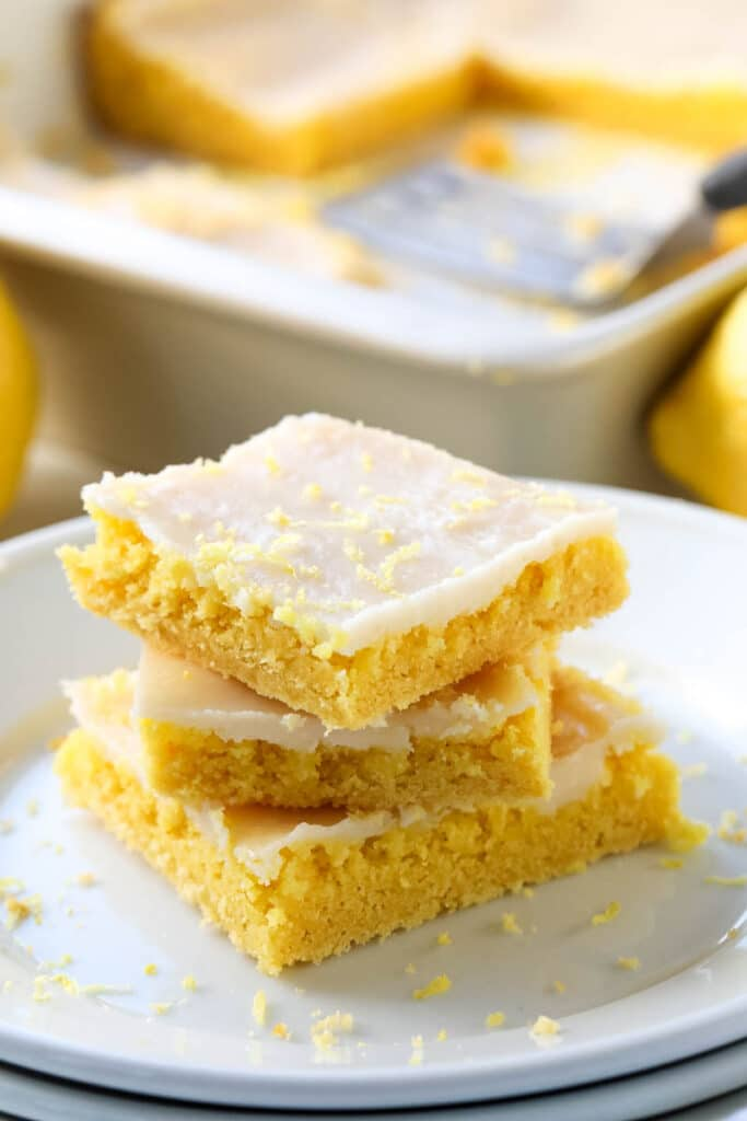 a stack of 3 lemon bars on a white plate