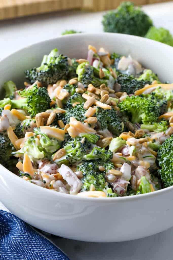 broccoli salad with dressing, cheese, and bacon bits in a white bowl.