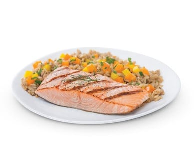 Fresh Atlantic Salmon served with rice and vegetables on a white plate Aldi.
