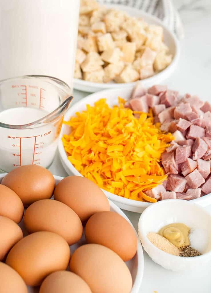 casserole ingredients - eggs, cheese, bread, milk, spices