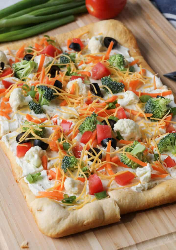 veggie pizza on a wooden cutting board