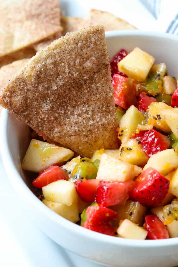 fruit salsa with cinnamon chips in a white bowl