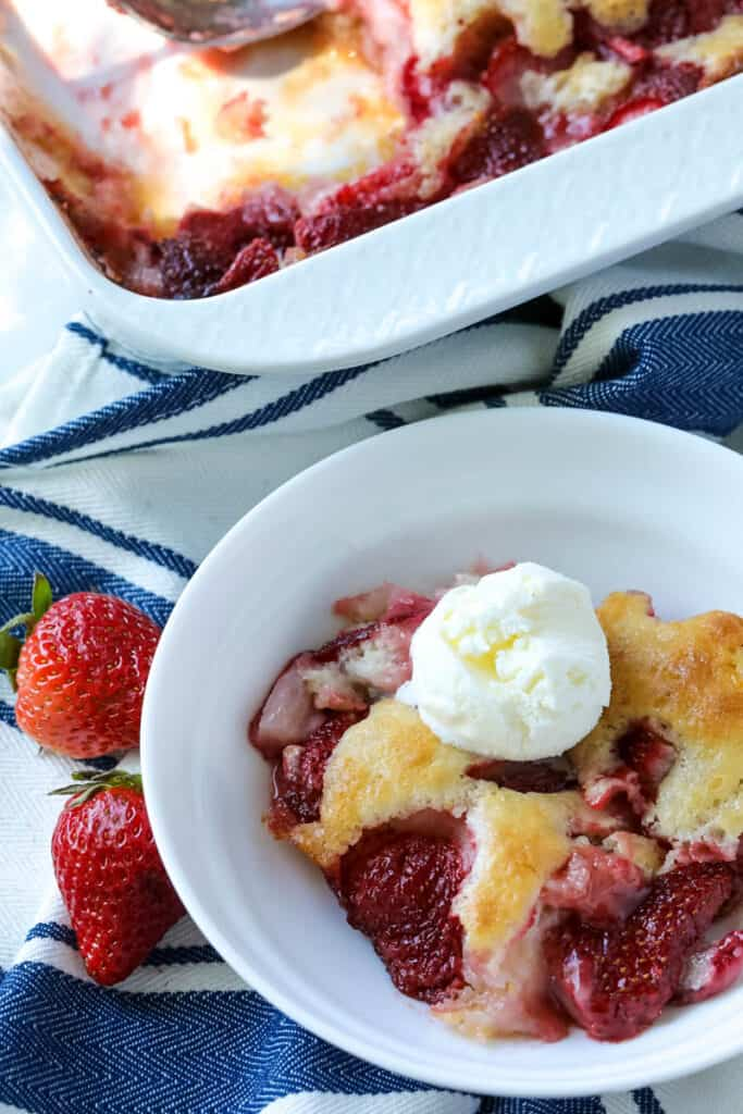 strawberry cobbler in a white dish on a table with a blue and white napkin