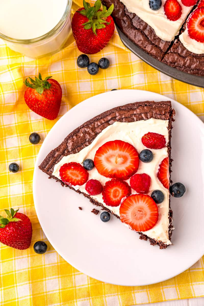 Slice of brownie fruit pizza topped with berries on a white plate on a yellow checkered picnic tablecloth with scattered berries, glass of milk and the brownie fruit pizza