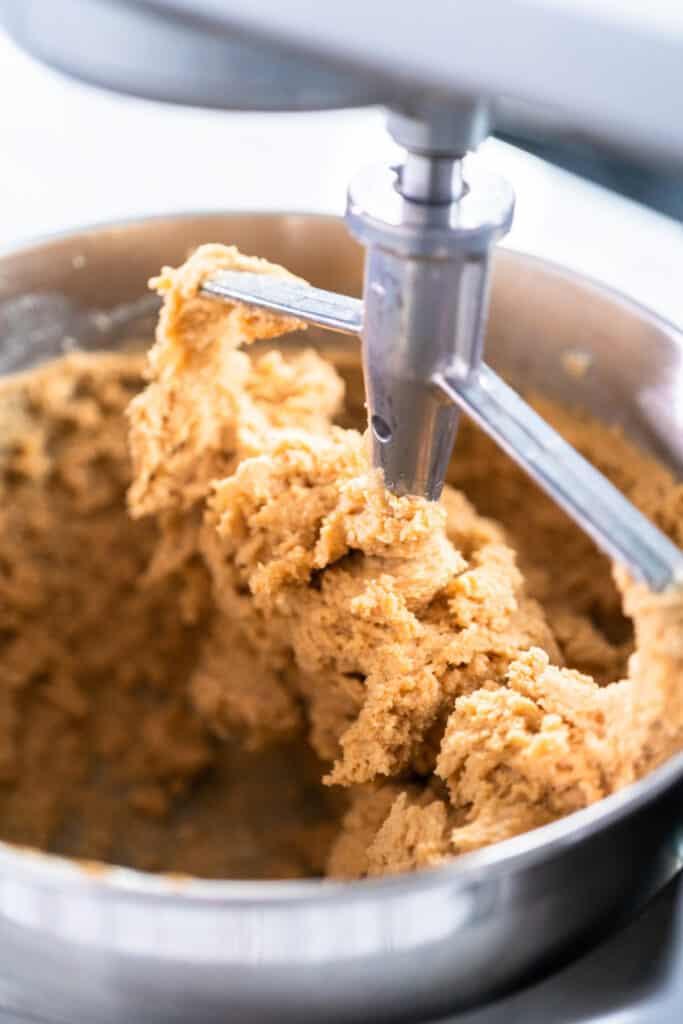 Mixing ingredients in standing kitchen mixer to bake peanut butter cookies.
