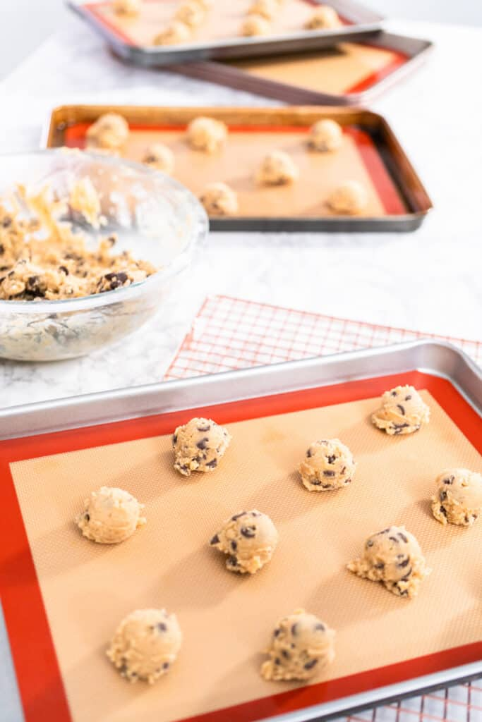 Homemade chocolate chip cookies dough scoops on a baking sheet with a silicone mat.