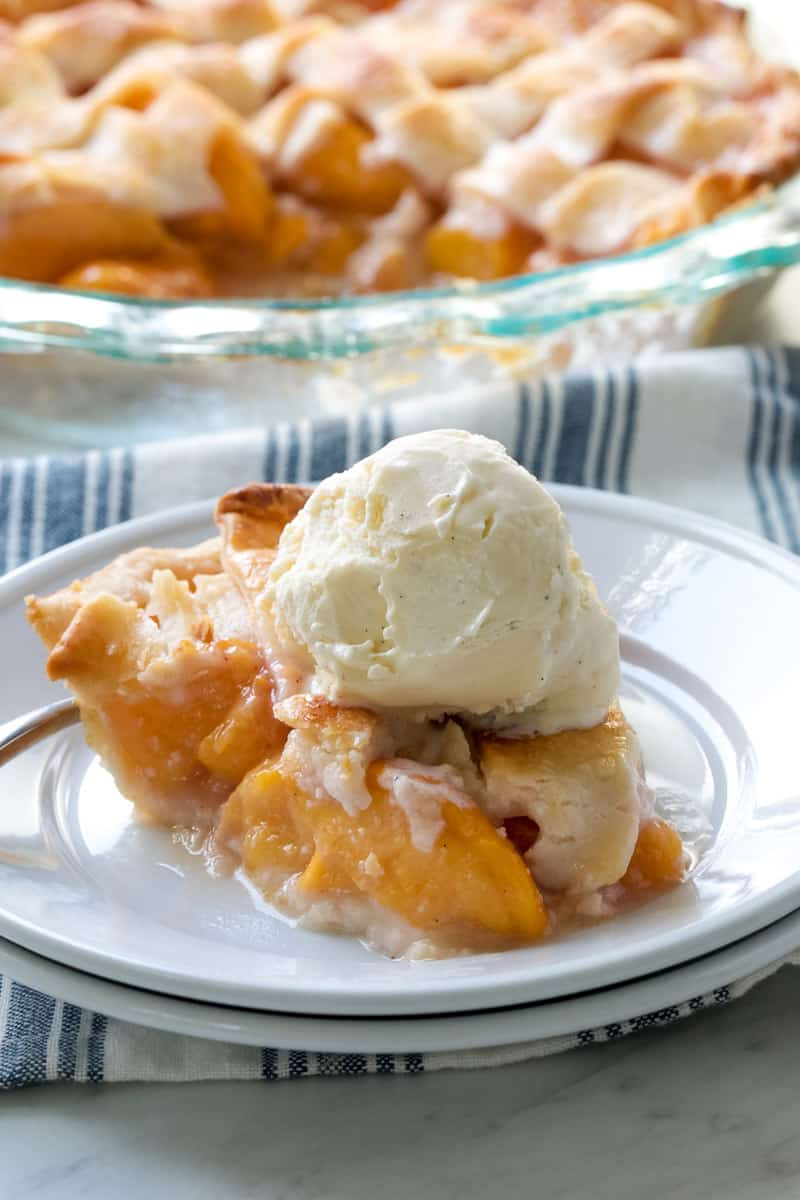 peach pie slice on a plate with a scoop of ice cream