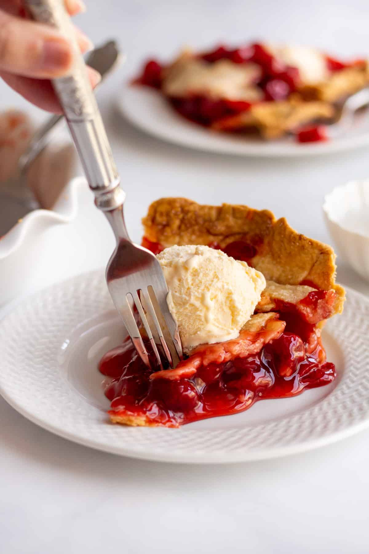 slice of cherry pie with a scoop of vanilla ice cream on top with a metal fork digging in