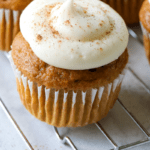 pumpkin spice cupcake with cream cheese frosting sitting on a wire cooling rack
