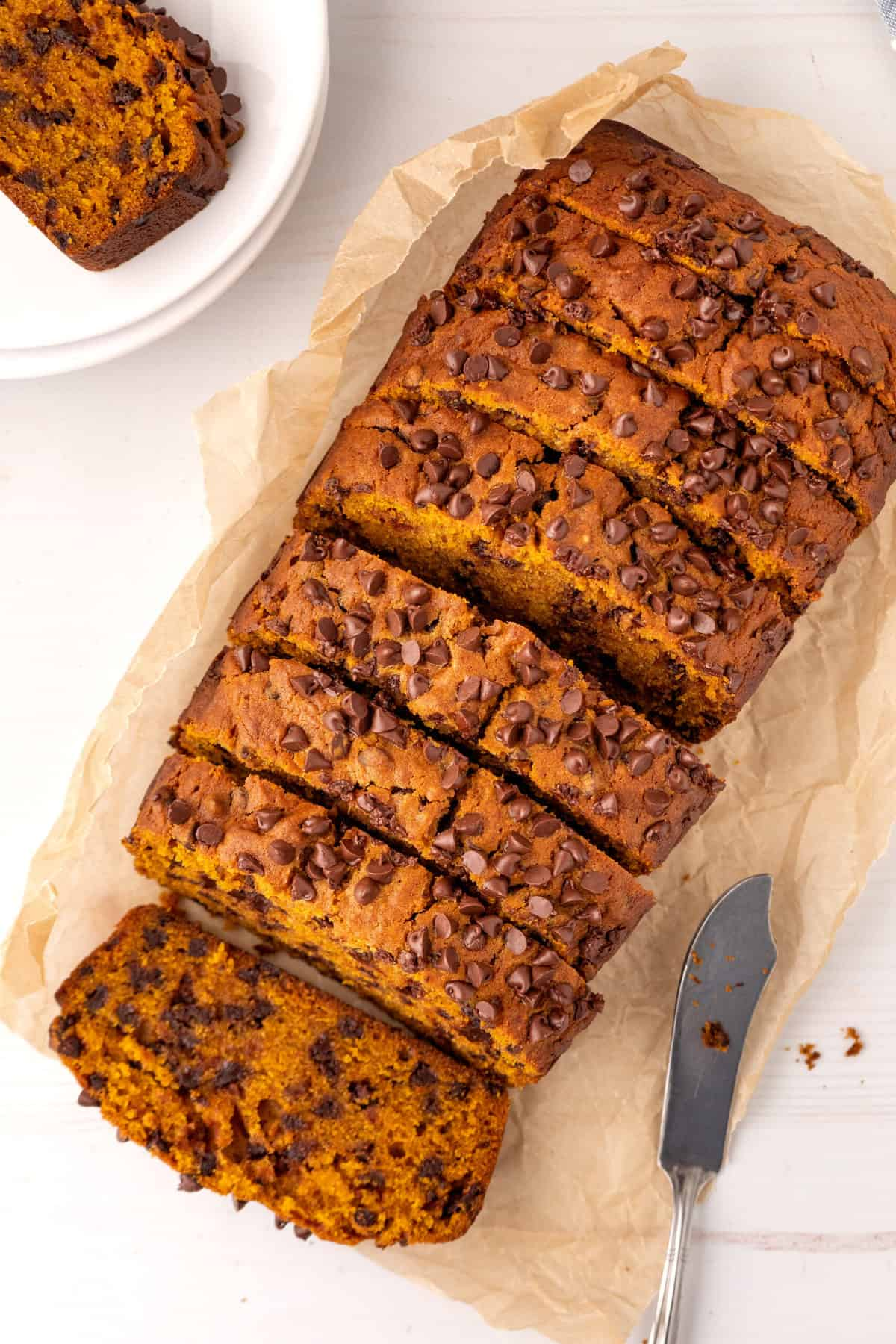 top view of sliced chocolate chip pumpkin bread served on parchment paper with a slice in the background served on a white plate