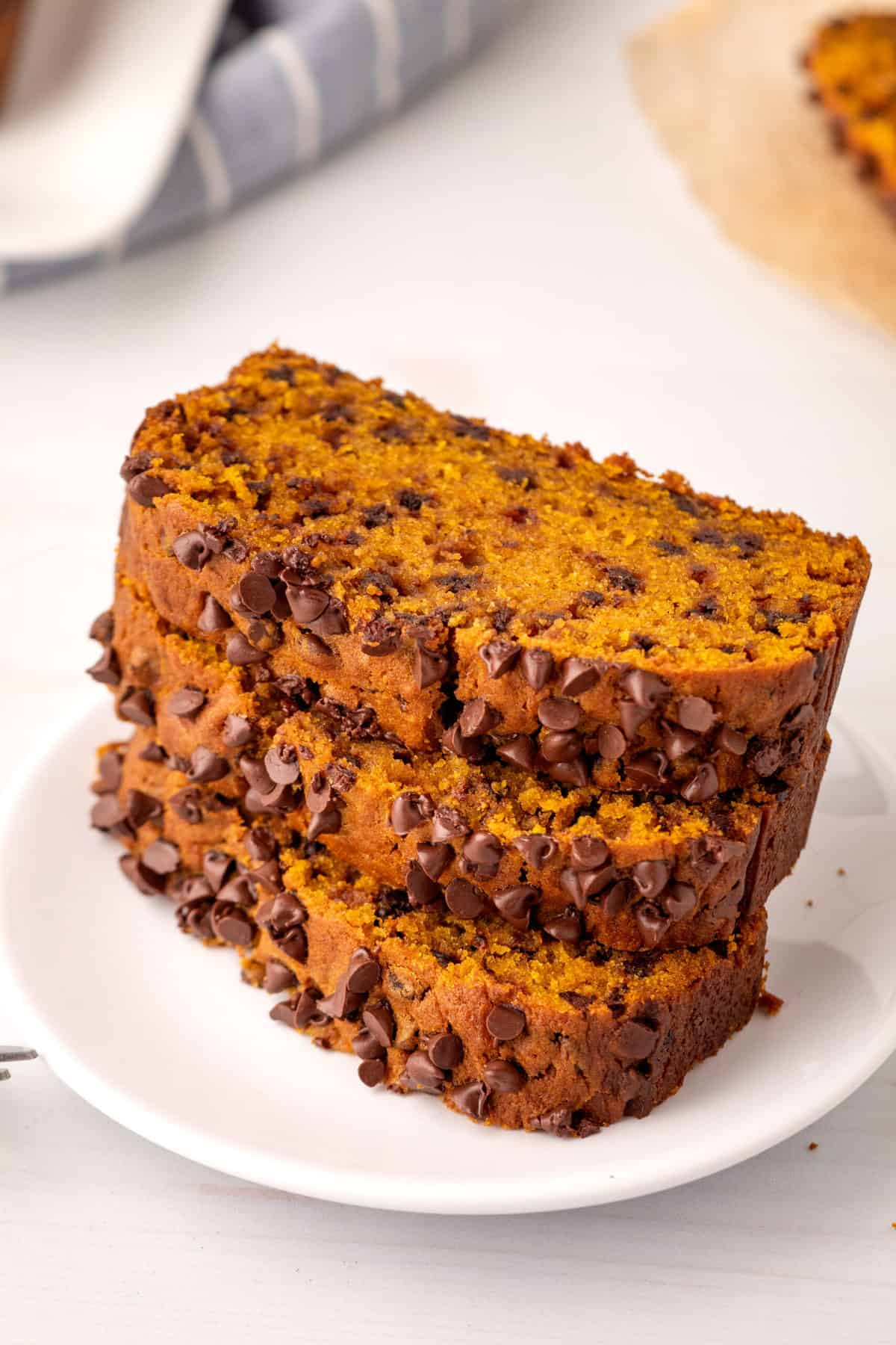 stack of three sliced chocolate chip pumpkin bread served on a white circle plate